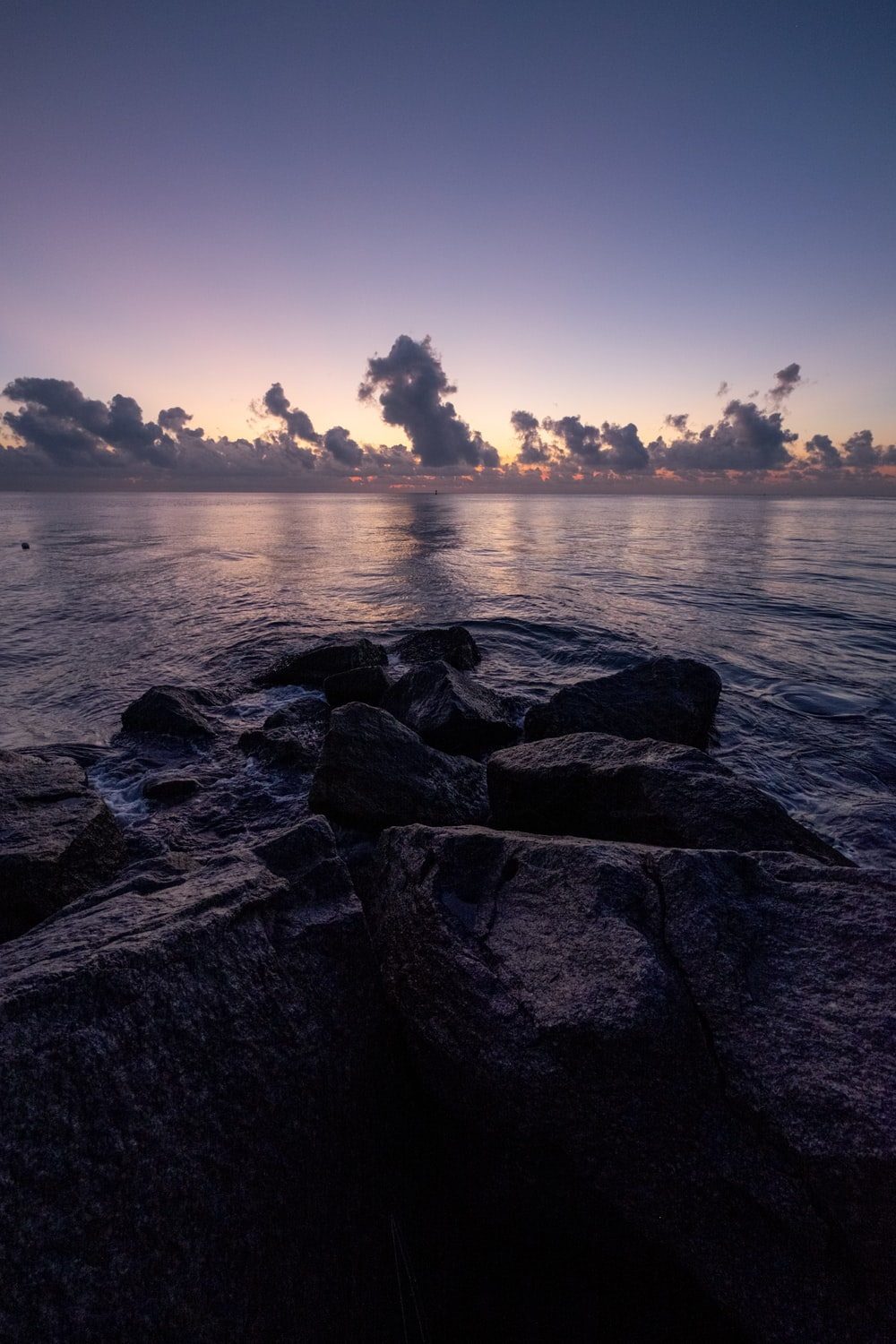 gray rocks near body of water during sunset