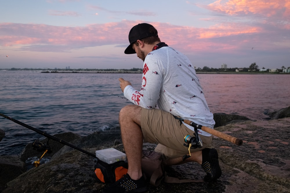 man in white long sleeve shirt sitting on black and brown fishing rod near body of on on on on