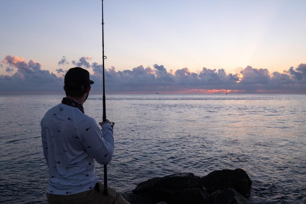 man in white dress shirt fishing on sea during sunset