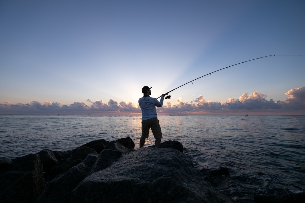 man in white t-shirt and brown shorts fishing on sea during daytime