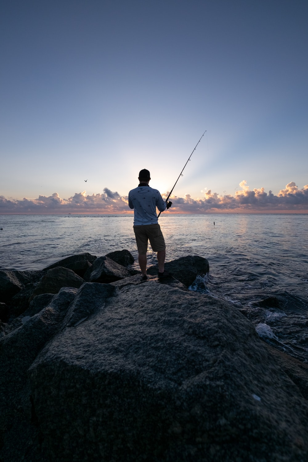 man in white shirt and brown shorts fishing on sea during daytime