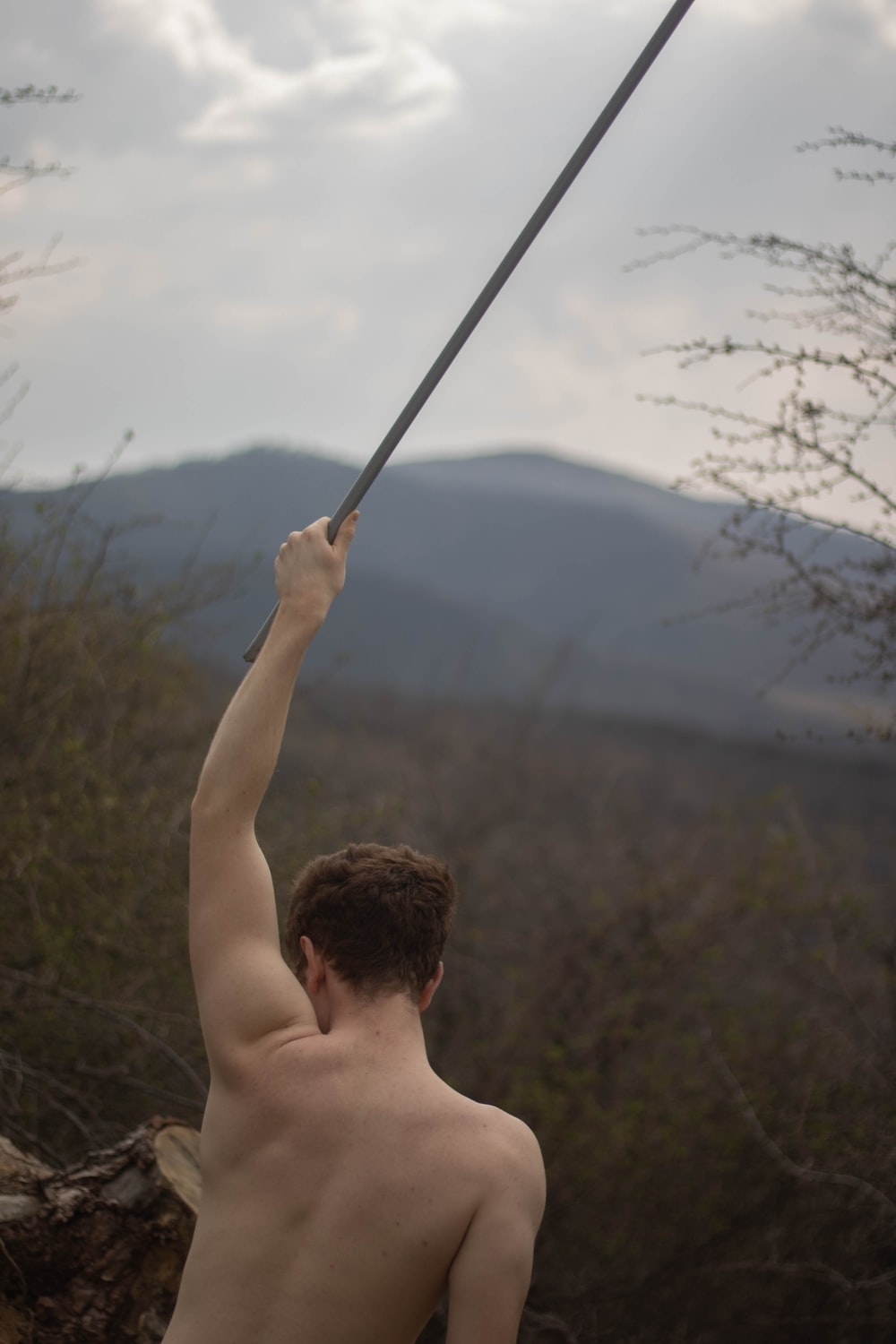 topless man holding stick during daytime