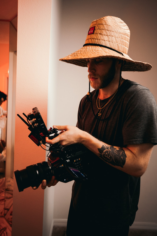 man in black crew neck t-shirt wearing brown cowboy hat holding black dslr camera