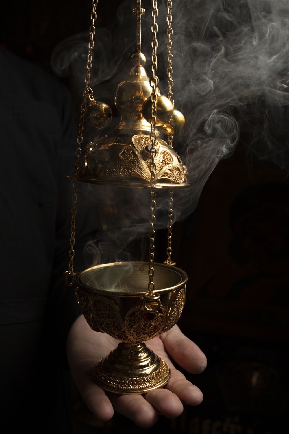 person holding gold colored vase with white smoke