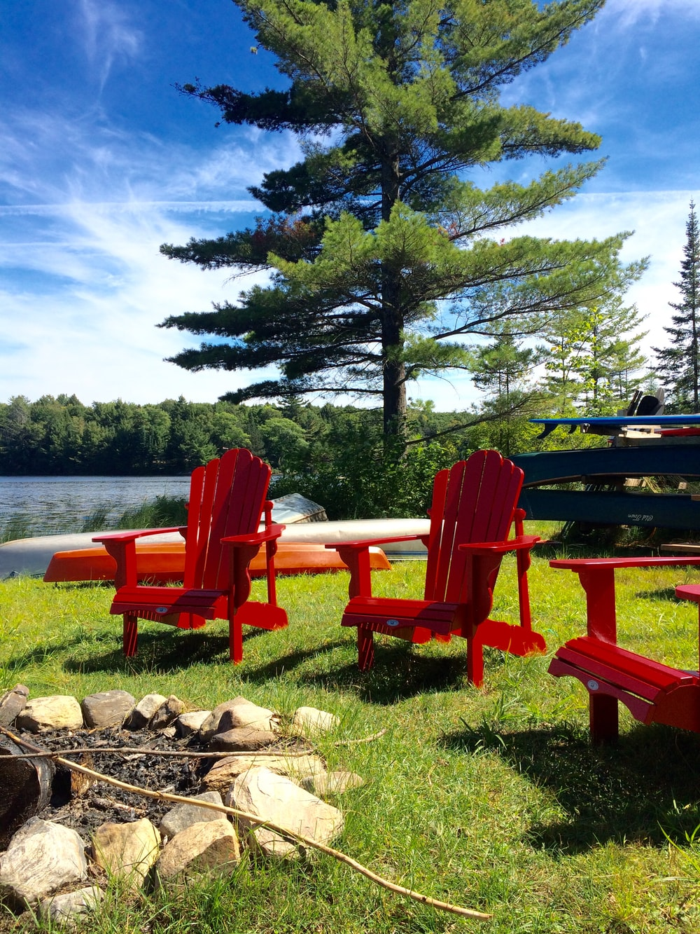 red wooden bench near body of water during daytime