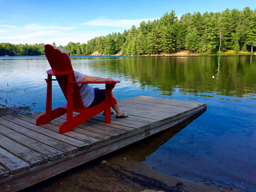 red wooden armchair on dock near lake during daytime