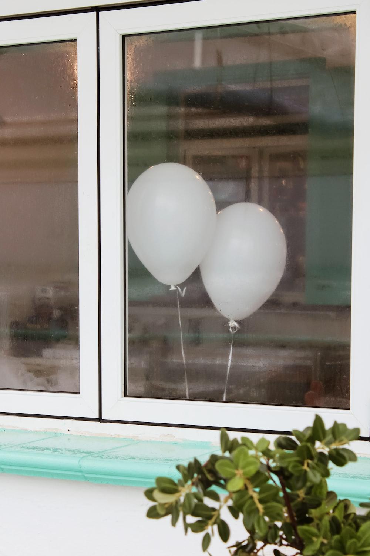 white balloons on glass window