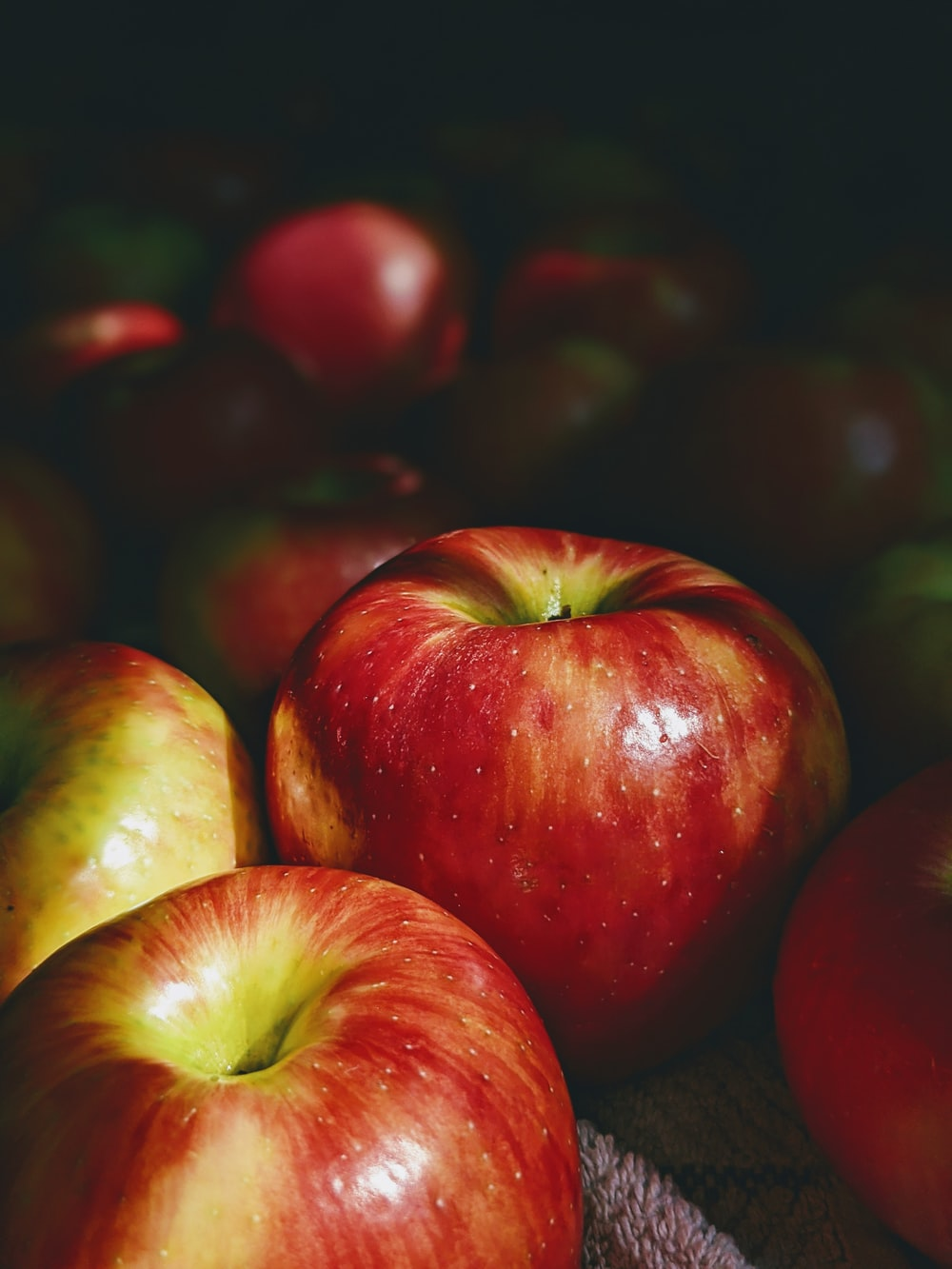 red and green apples on black surface