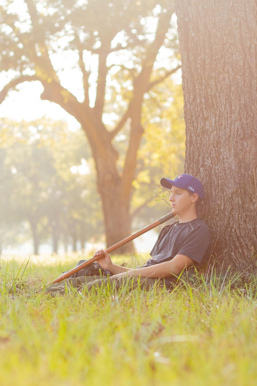 man in black shirt sitting on green grass field during daytime