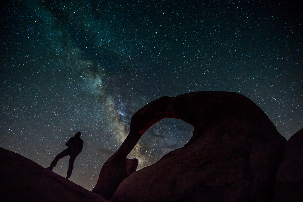 silhouette of man and woman standing on rock formation during night time