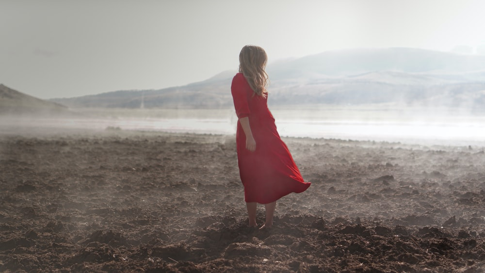 woman in red dress standing on brown soil during daytime