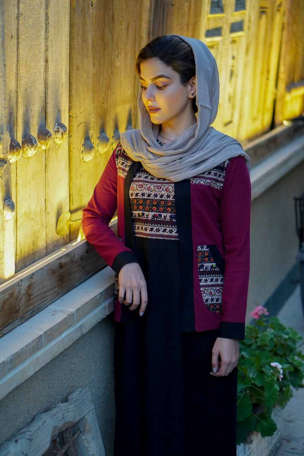woman in red long sleeve dress wearing brown hijab standing beside yellow wooden door during daytime