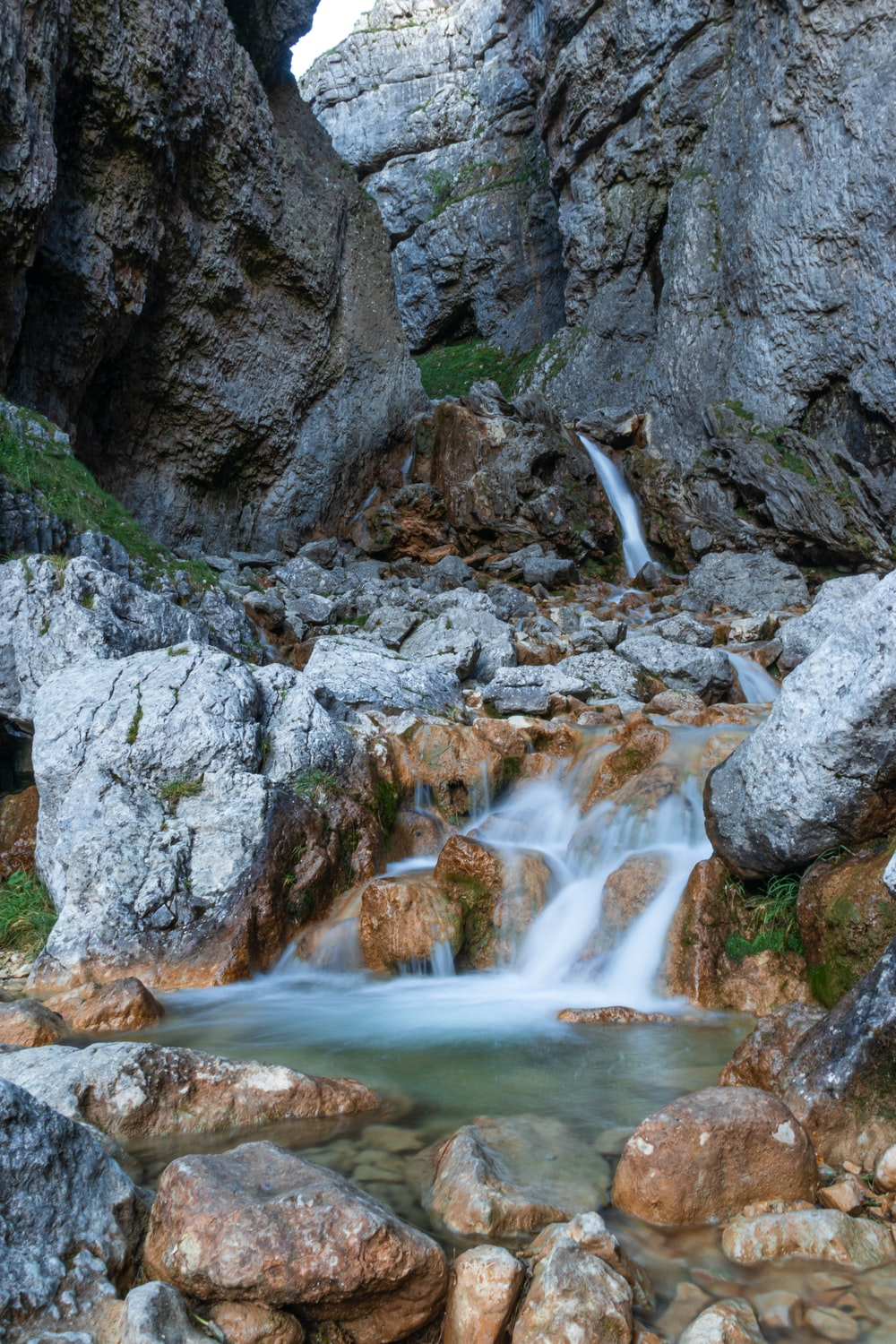water falls between gray rocky mountain during daytime