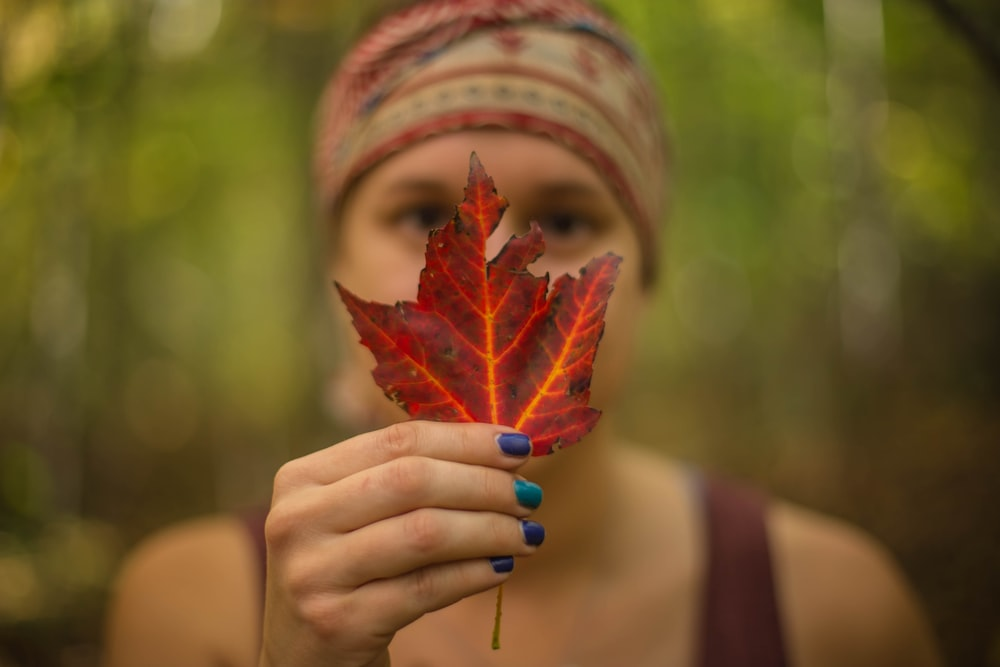 woman holding red maple leaf