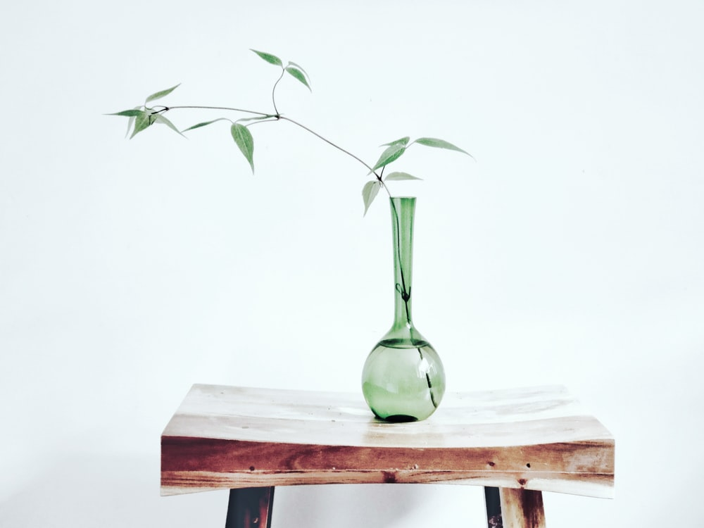 green glass vase on brown wooden table