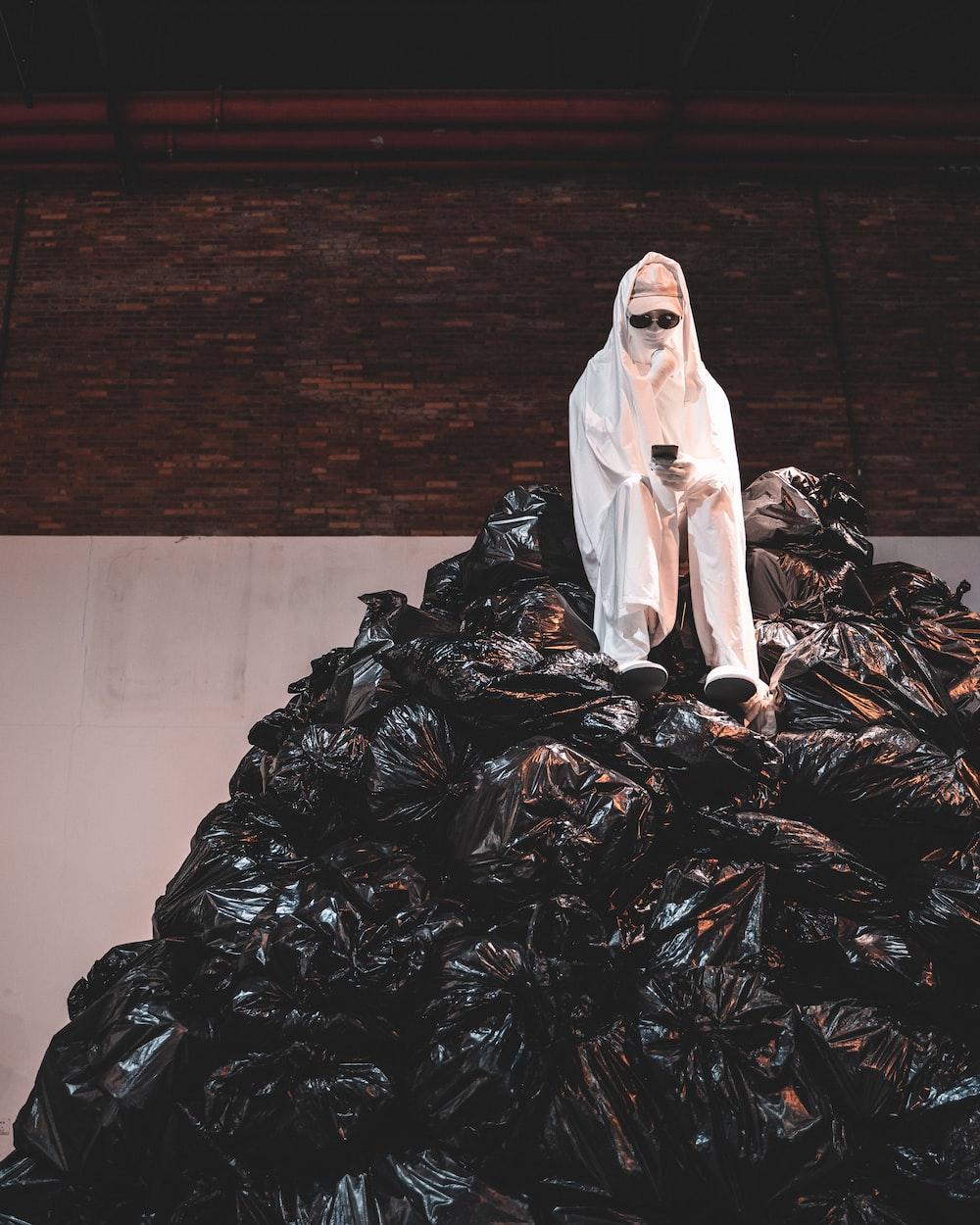 woman in white dress sitting on black plastic bag