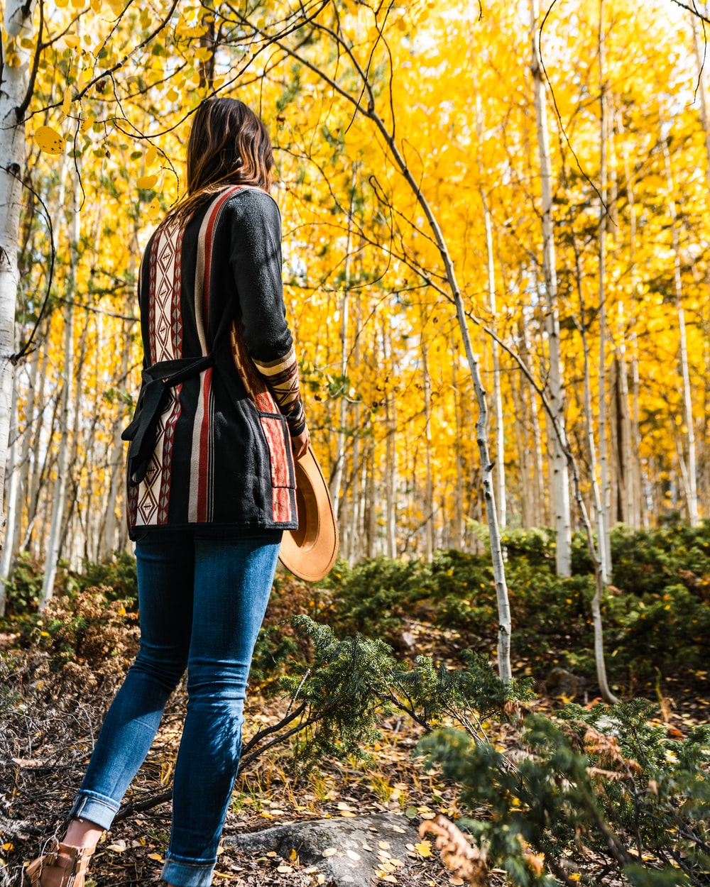 woman in black leather jacket and blue denim jeans standing on forest during daytime