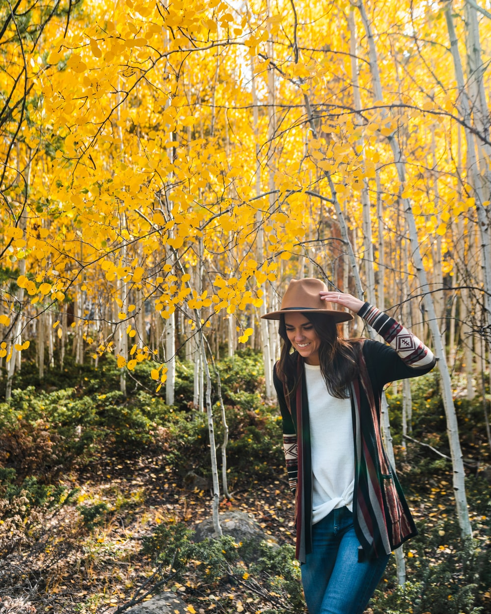 woman in white long sleeve shirt and brown hat standing near yellow leaf trees during daytime