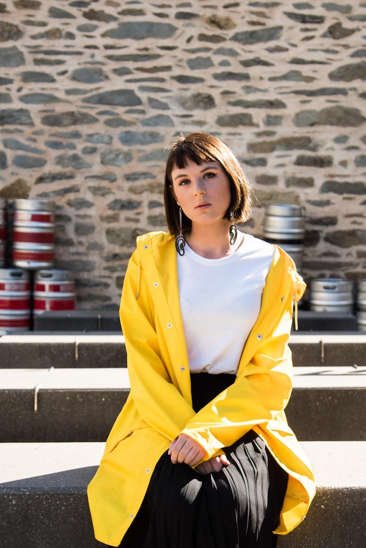 woman in yellow blazer sitting on gray concrete bench