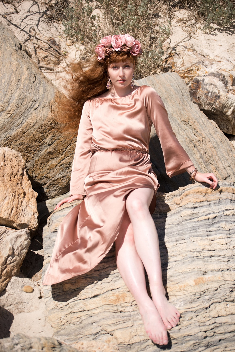 woman in pink sleeveless dress sitting on brown rock