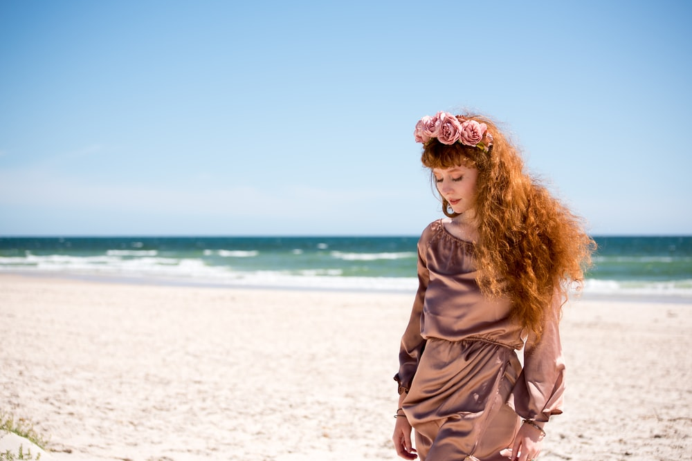 woman in brown long sleeve shirt standing on white sand during daytime