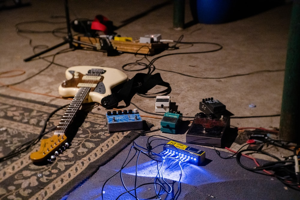 white electric guitar on blue guitar amplifier