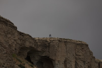 person standing on brown rock formation during daytime afghanistan zoom background