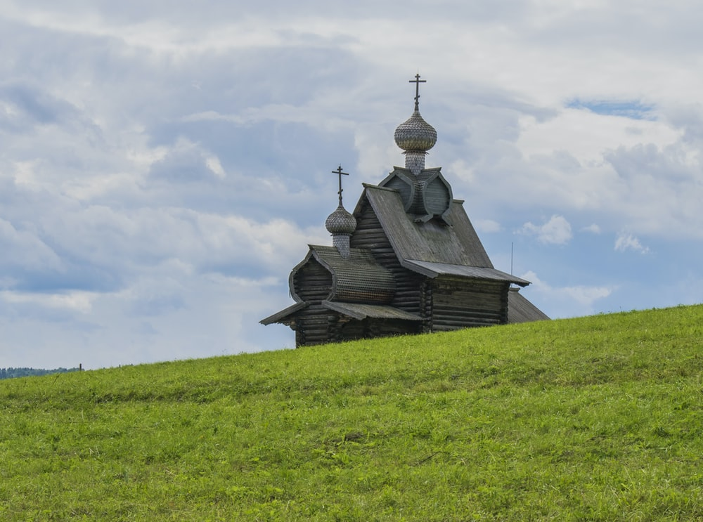 black wooden house on green grass field under white clouds during daytime