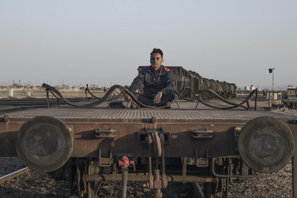 man in black jacket sitting on brown metal train rail during daytime