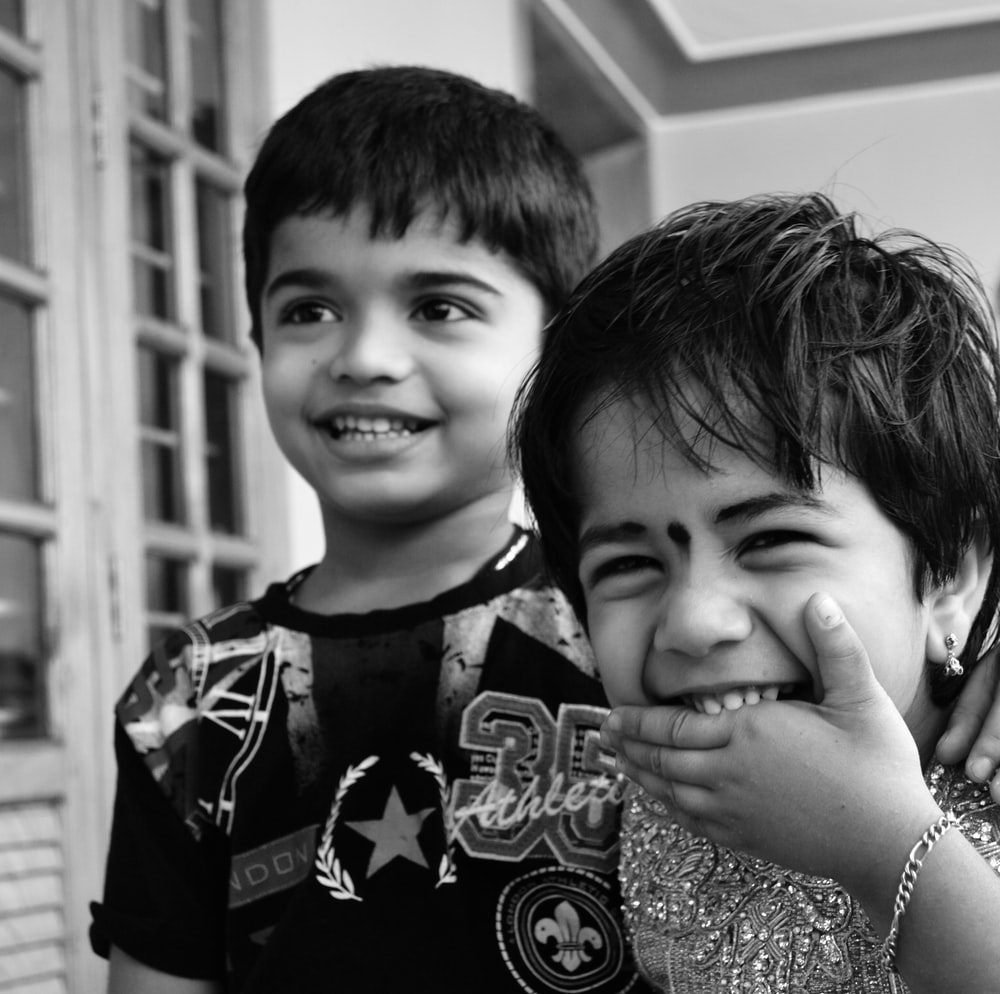 grayscale photo of 2 boys smiling