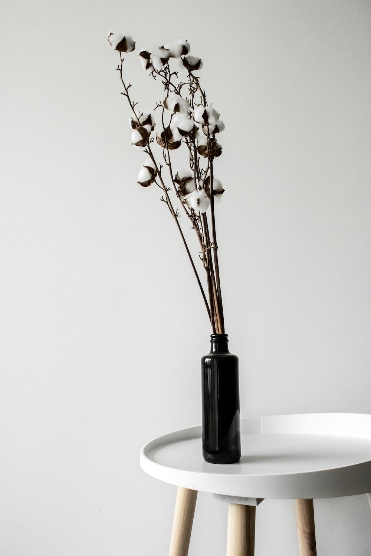 white flowers in black glass vase