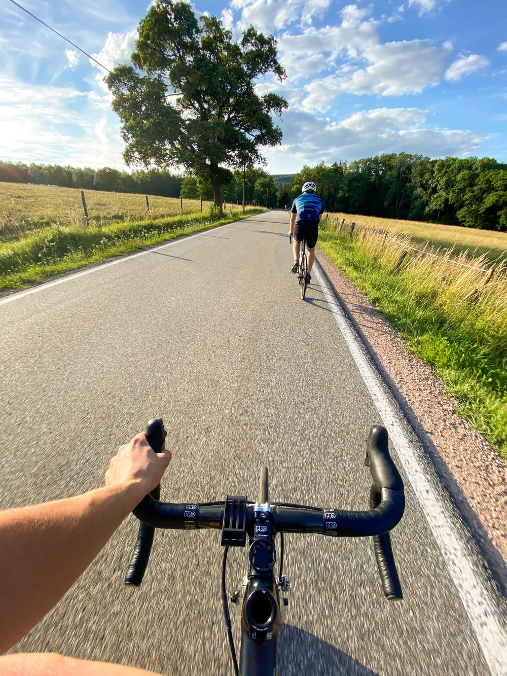 man in black t-shirt and blue denim jeans riding bicycle on road during daytime
