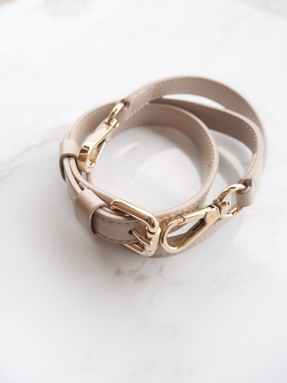 gold and silver bracelet on white surface
