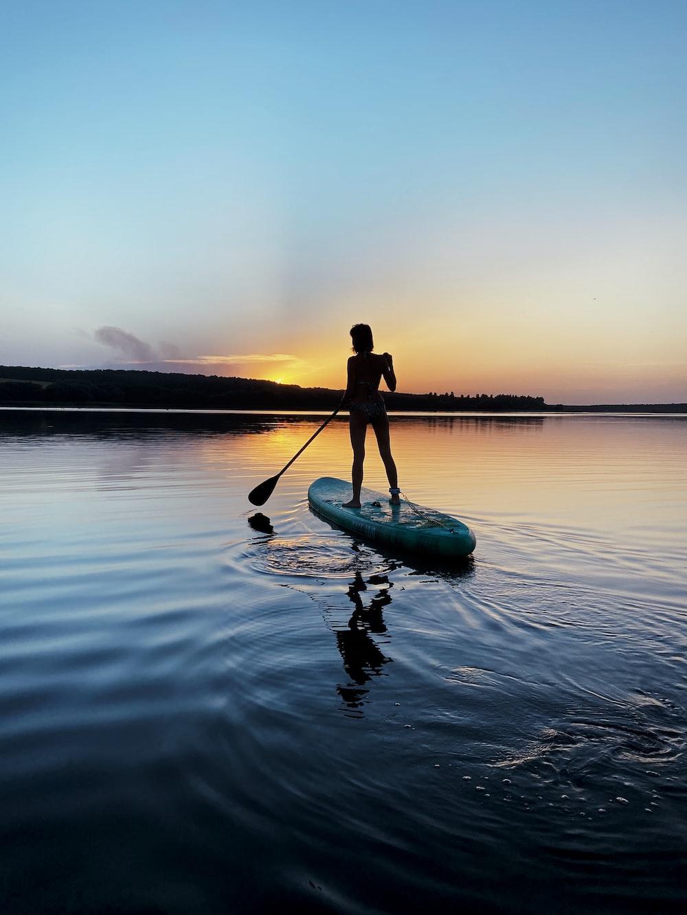 man in black shirt riding on green kayak on body of water during daytime