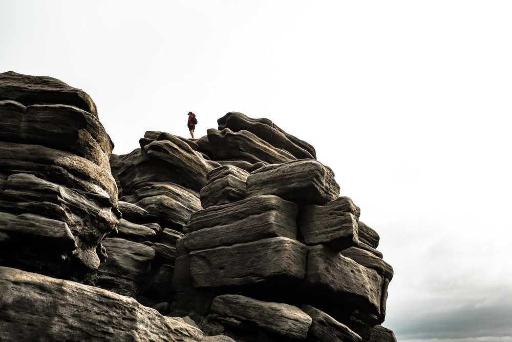 person in black jacket standing on rock formation during daytime