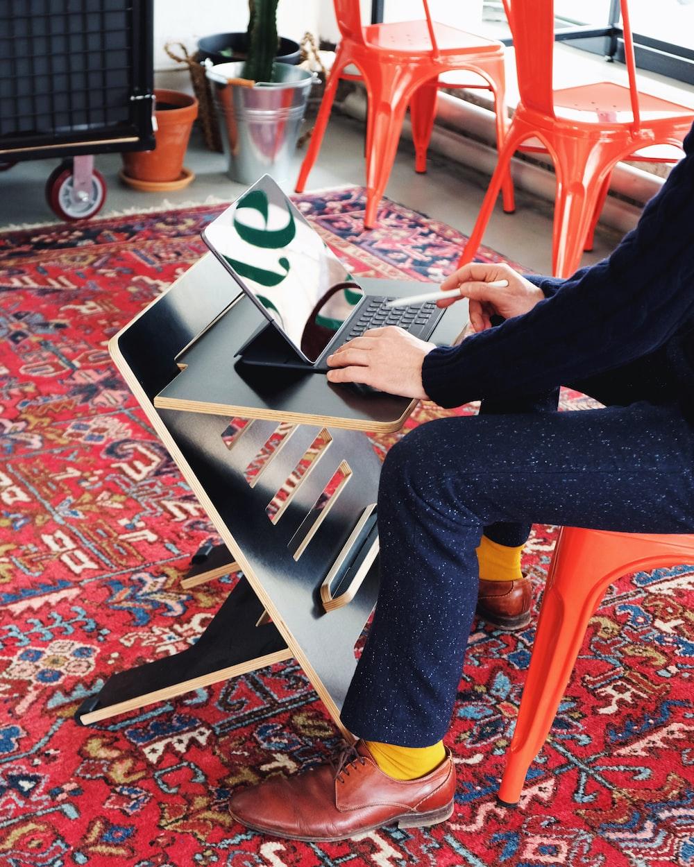 person in black pants sitting on orange plastic chair reading magazine
