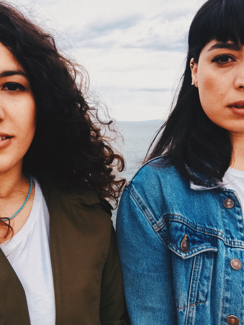 woman in blue denim button up jacket beside woman in white shirt