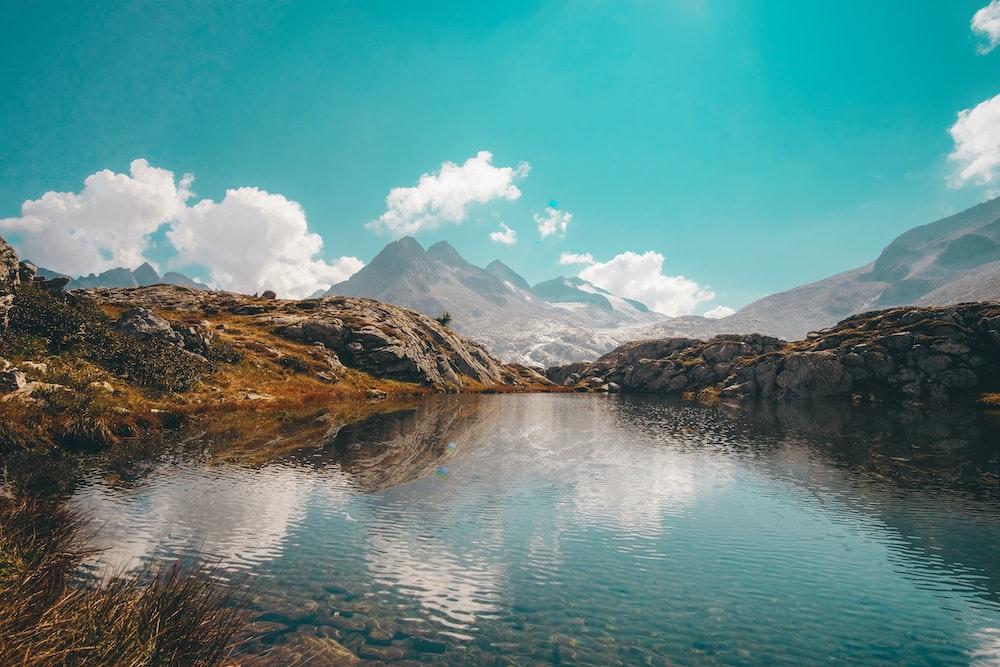 lake near mountain under blue sky during daytime