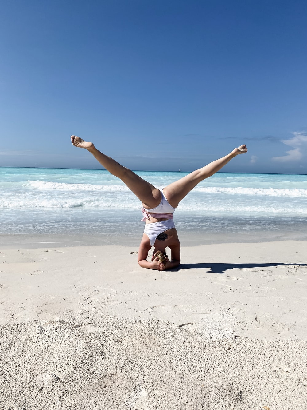woman in white tank top and white shorts jumping on beach during daytime