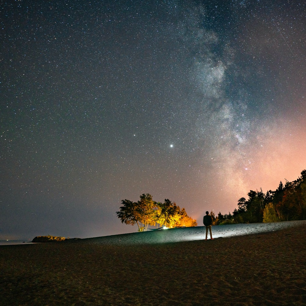 person standing on brown sand under starry night
