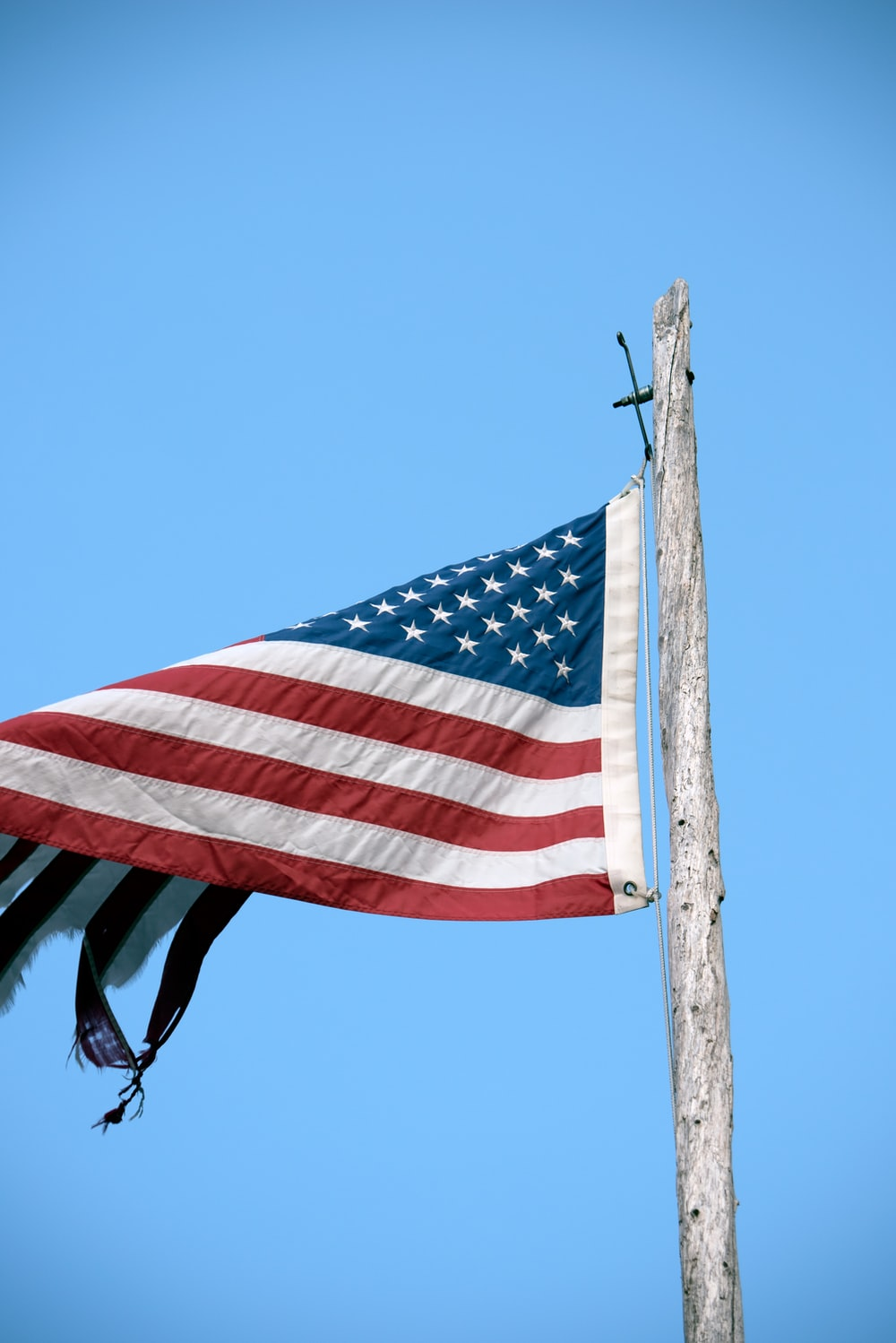 us a flag on brown wooden pole during daytime