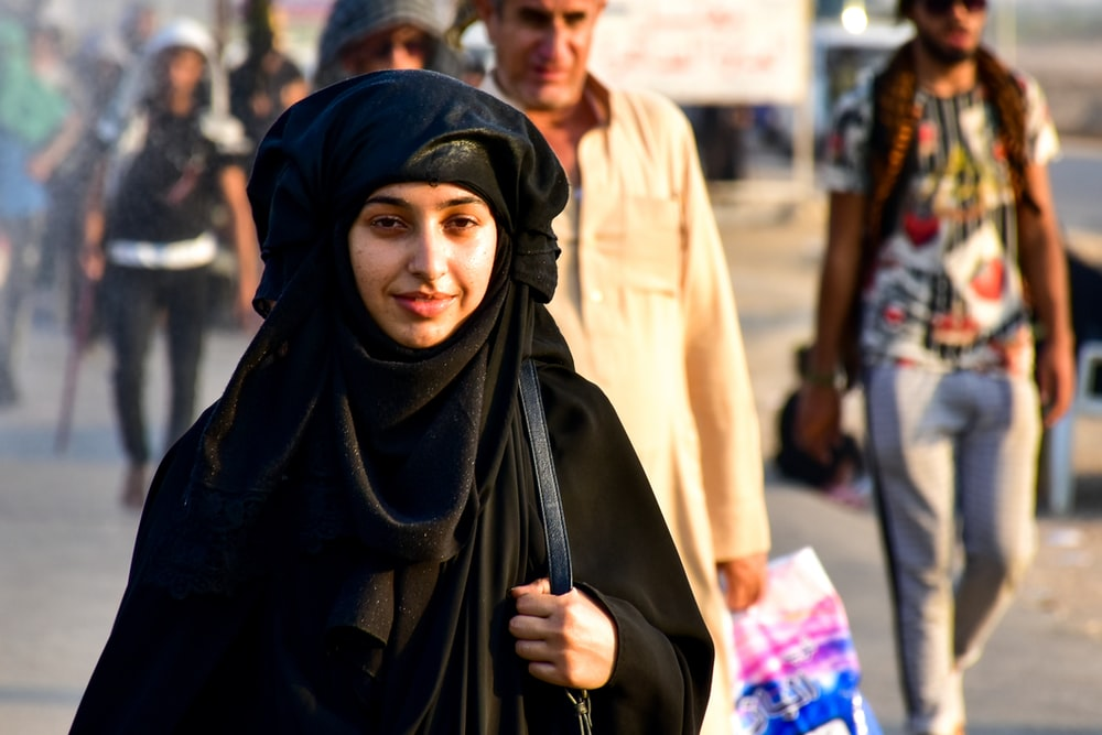 woman in black hijab standing near people during daytime