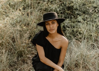 woman in black off shoulder dress wearing black hat sitting on brown grass field during daytime
