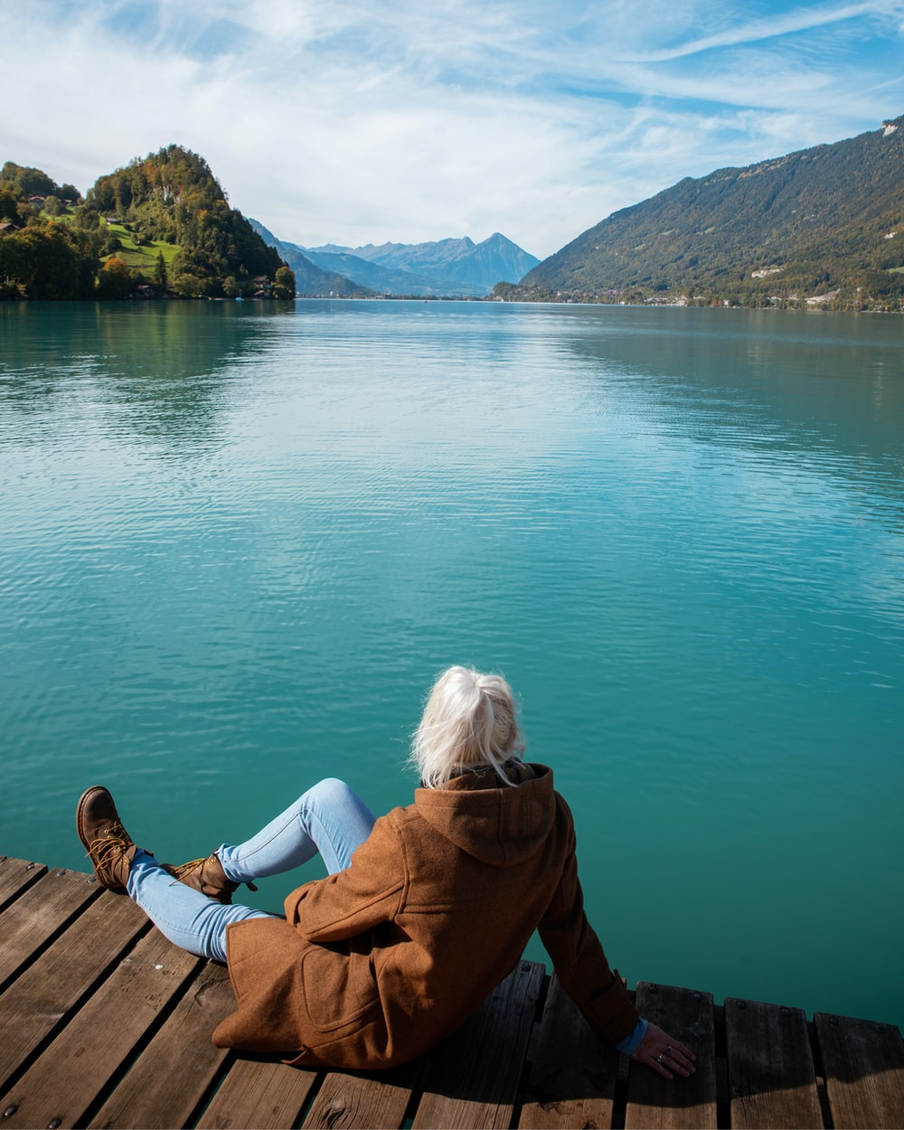 woman in brown jacket sitting on brown wooden dock during daytime
