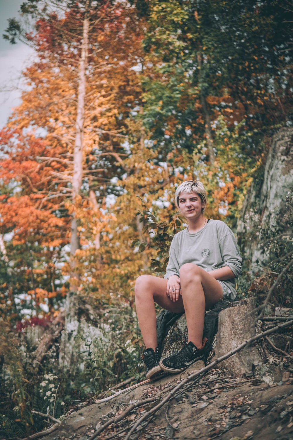 woman in gray crew neck t-shirt sitting on brown rock during daytime