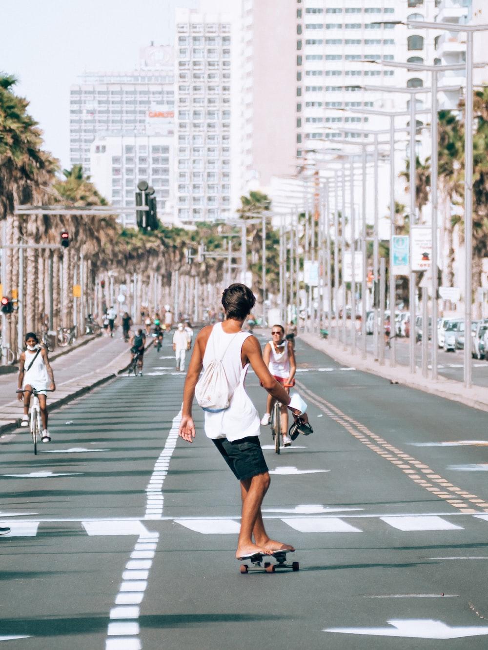 man in white tank top and black shorts running on pedestrian lane during daytime