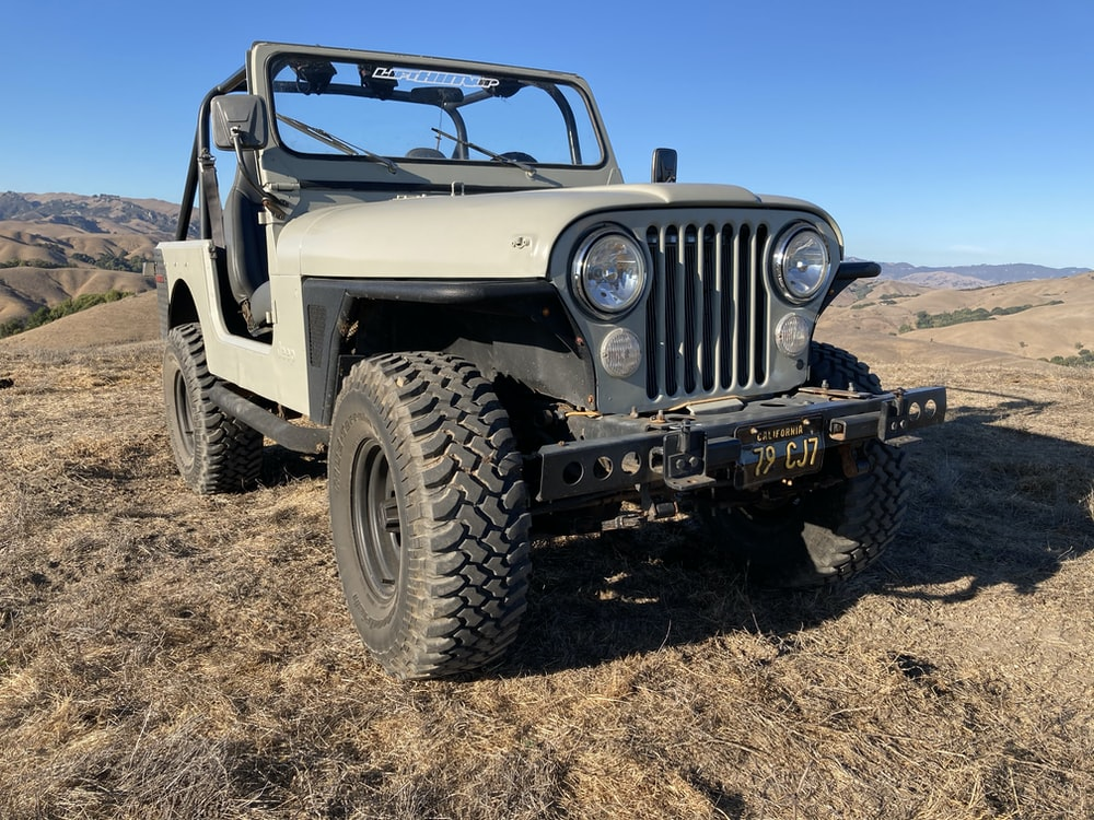 white and black jeep wrangler on brown sand during daytime