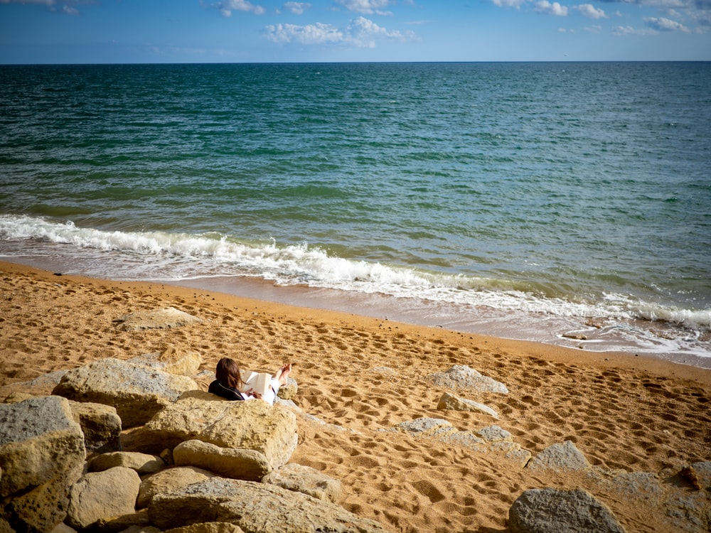 person in white shirt sitting on brown rock near sea during daytime