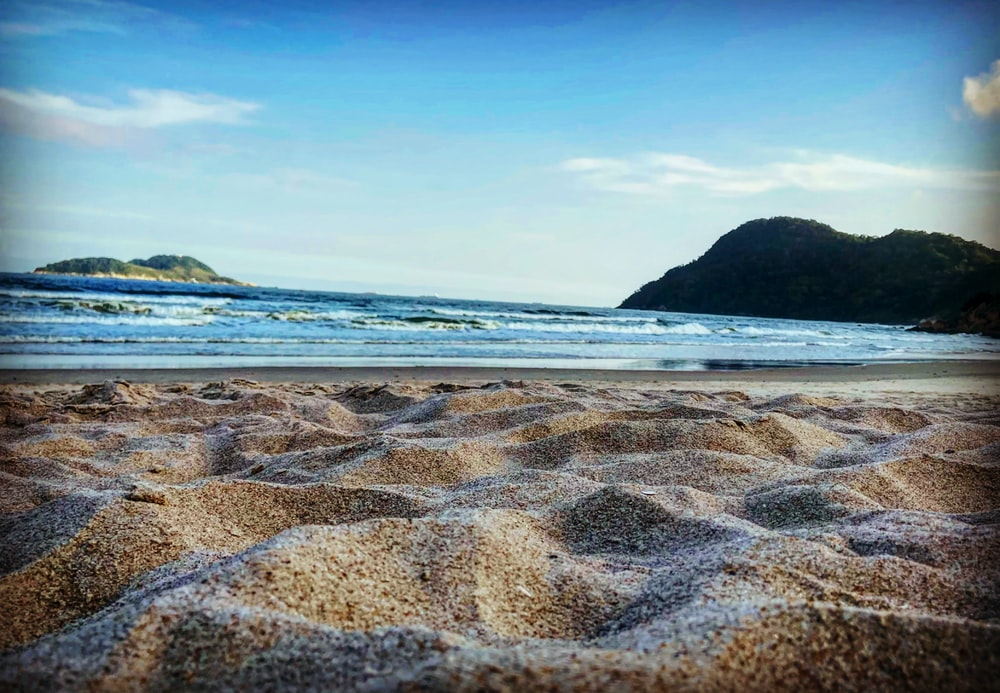 brown sand beach with blue ocean water during daytime