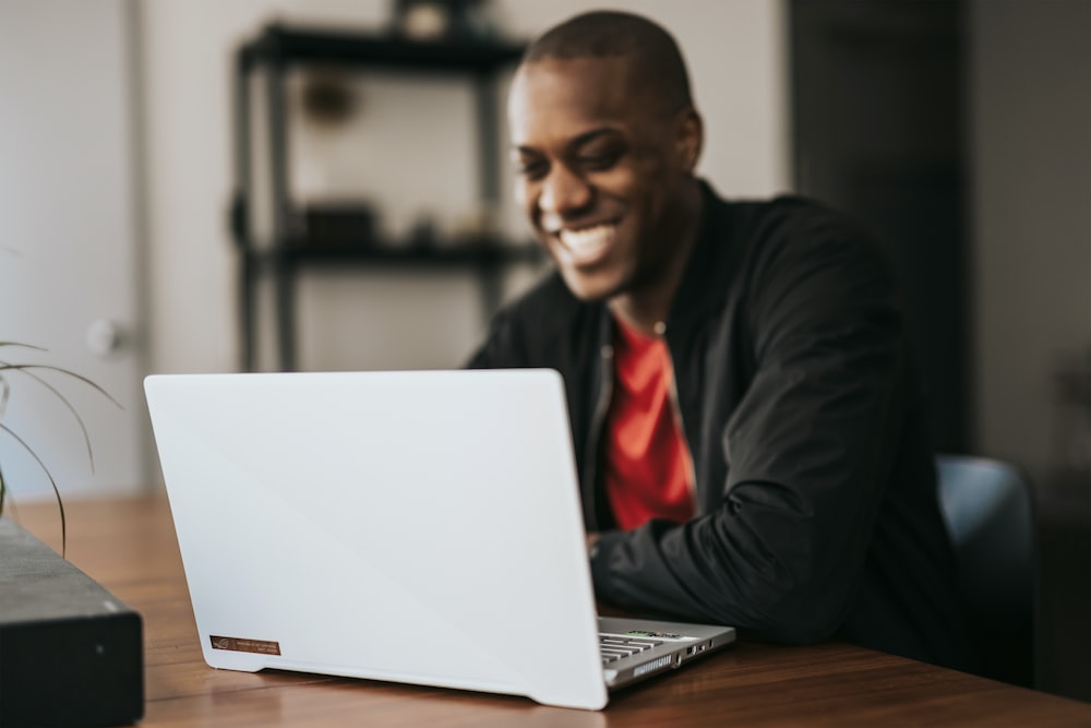 man in black blazer sitting by the table with macbook